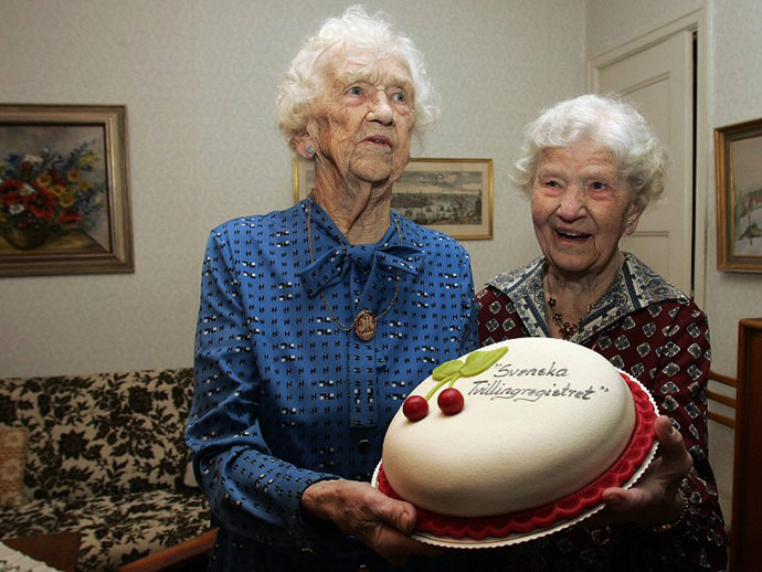 "100-year-old Swedish twins Gunhild Gaellstedt (L) and Siri Ivarsson (R) with a cake from the ""Twinregistry"" as they holds their long lifes first pressconference in their home in Stockholm 28 January 2005. The birthday is on Sunday 30 January. The two are the oldest twins in Sweden that according to the Twinregistry, counts to 86 000 couples. The two manage their daily life without a permanent assistance. They will celebrate their 100th birthday on 30 January 2005."