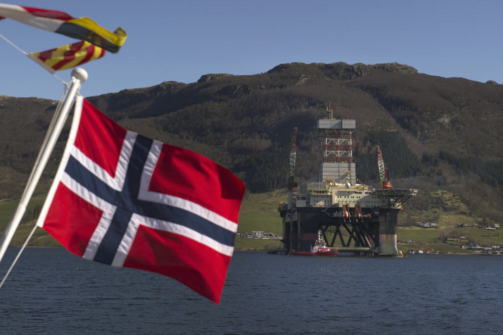 A Norwegian national flag flies from a vessel near the Scarabeo 8 deepwater oil drilling rig, operated by ENI Norge AS, in Olensvag, Norway, on Tuesday, April 3, 2012. The world's seventh-largest oil exporter boasts no net debt, adding to its appeal as an alternative to the debt-riddled euro area. Photographer: Kristian Helgesen/Bloomberg