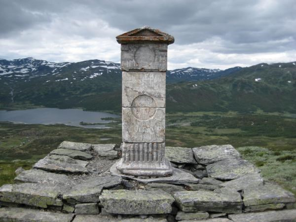 The cache is placed at Mureklopphaugen, about 14 meters southwest of the old county border stone between the old Bergen and Akerhus counties. The stone is made of Danish marble and was placed here in 1797 by C. J. Hammer who built the road.