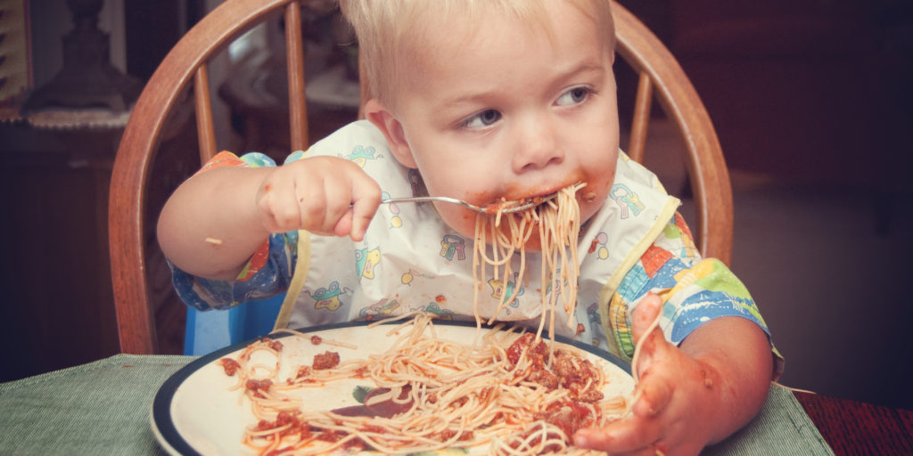 Danish boy feeding himself spaghetti